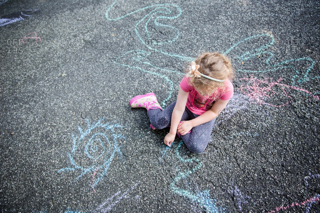 A girl chalk drawing on ground