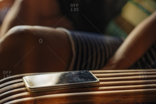 A smartphone on arm of chair