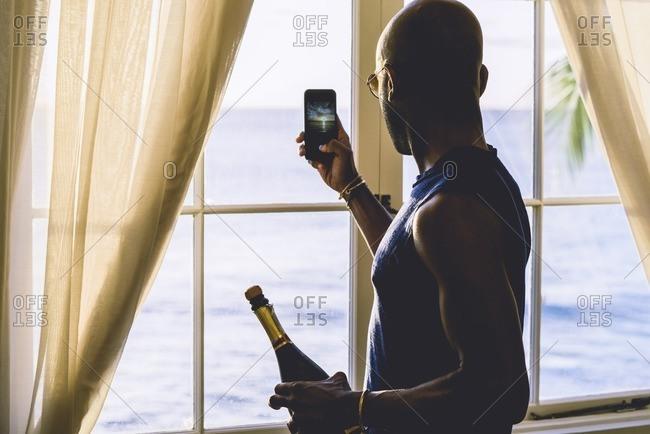 Man taking ocean photo at window
