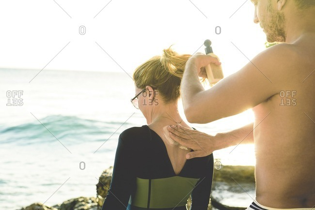 Man helping woman with sunscreen