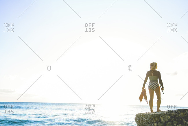 Woman with flippers on sea wall