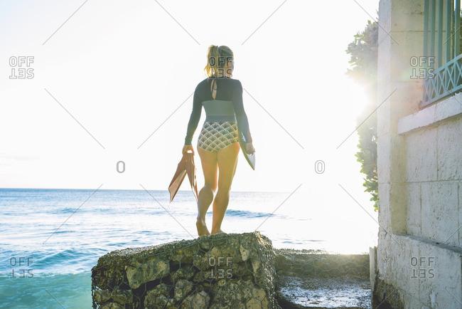 Woman walking sea stone wall