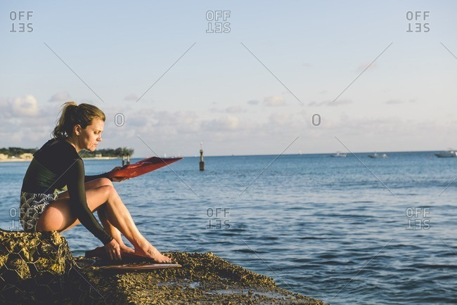 Woman putting on flippers by sea