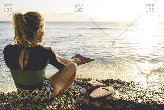 Woman putting on flippers by ocean