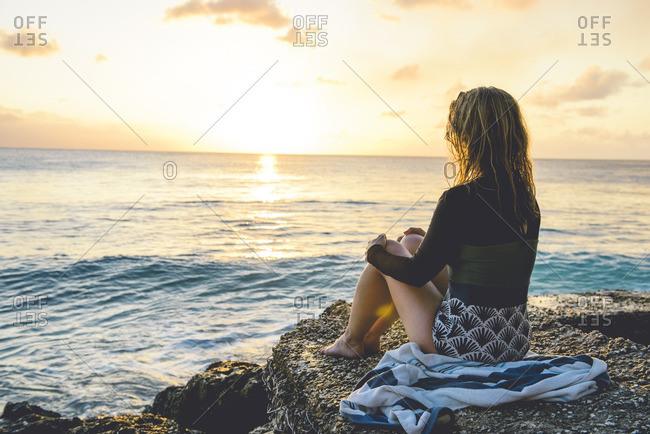 Woman watching sun over ocean