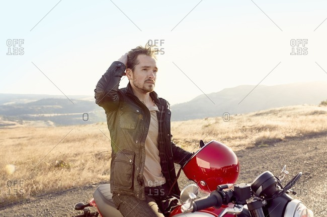 Man with motorbike in hills