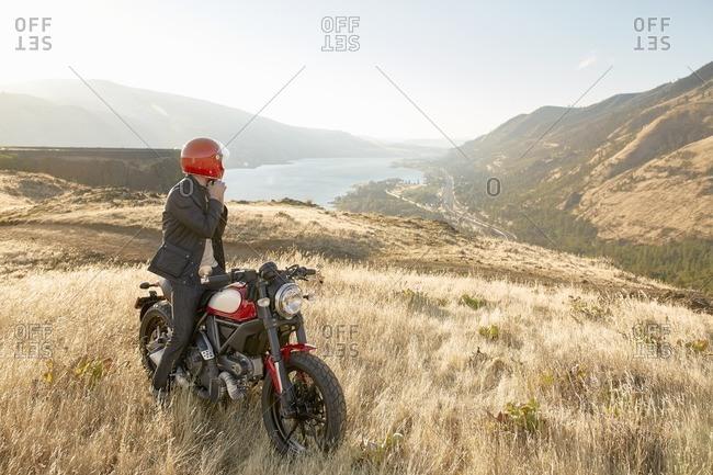 Man on motorcycle overlooking valley