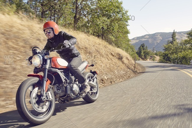 Man riding motorbike through hill setting