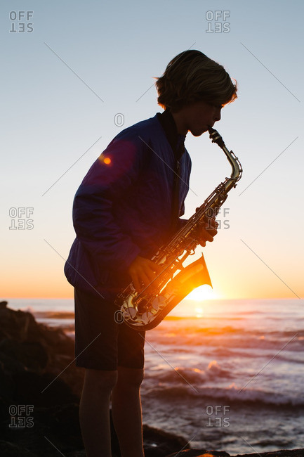 Boy playing saxophone on the beach at sunset