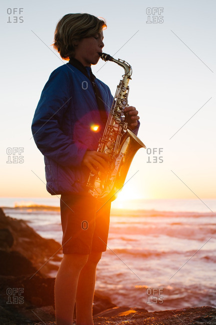 Young boy playing saxophone on the beach at sunset