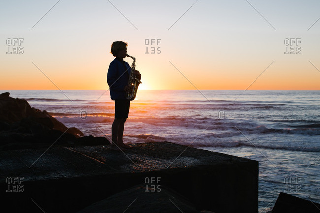 Silhouette of boy playing saxophone by the ocean at sunset