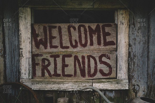 Wood sign with the words 'Welcome Friends' in an old barn window