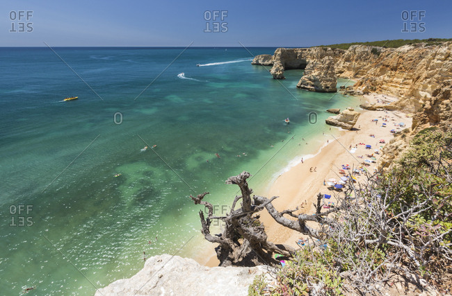 Tourists on sandy beach at Praia da Marinha surrounded by turquoise ocean, Caramujeira, Lagoa Municipality, Algarve, Portugal, Europe