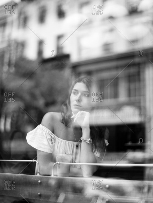 Young woman looking out a coffee shop window