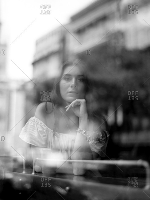 Portrait of a young through a coffee shop window