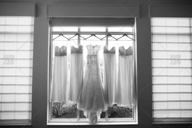 Wedding gown and bridesmaid dresses hanging in a window