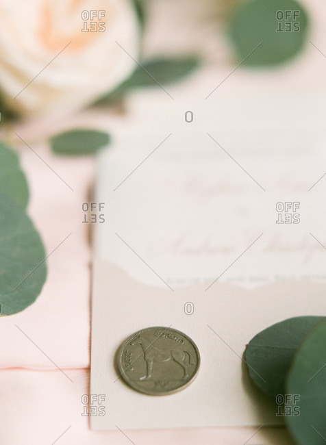 Irish coin and white rose on a wedding invitation