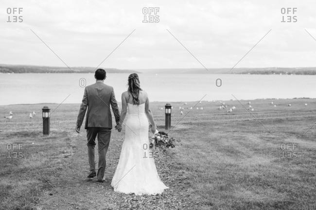 Bride and groom walking towards seashore