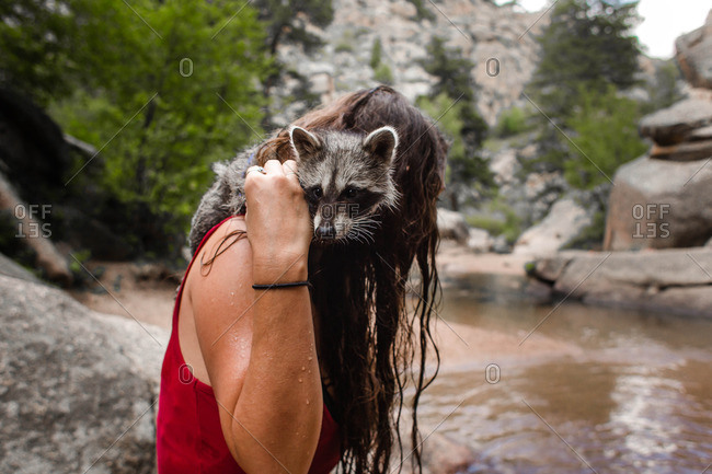 Woman holding a raccoon at the edge of a mountain creek