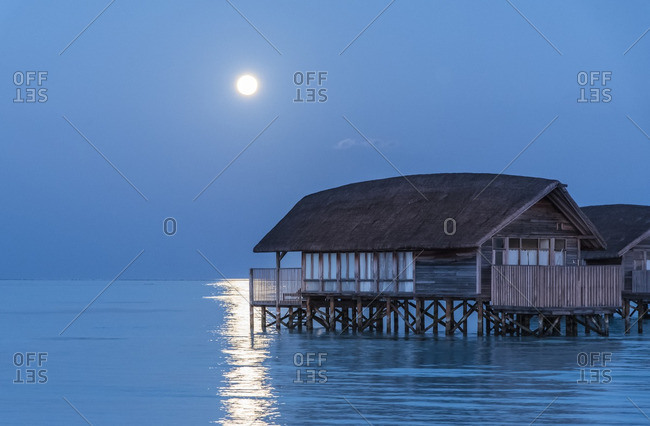 Thatched roof huts on stilts along a beach