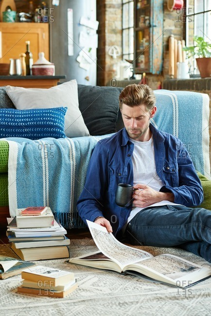Man sitting on the floor of his living room enjoying a cup of coffee and a book