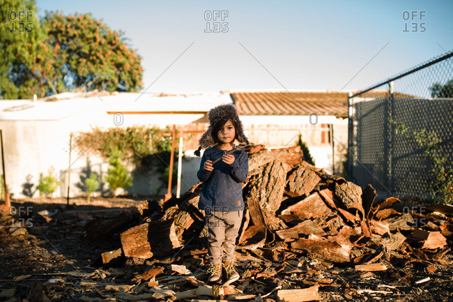 Child holding a stick and standing in front of a wood pile
