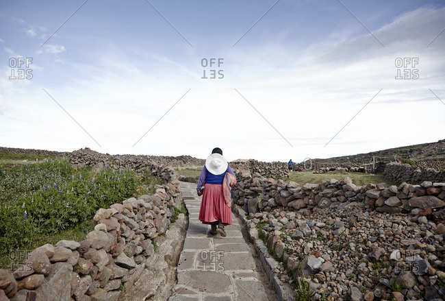 Peruvian woman walking on path