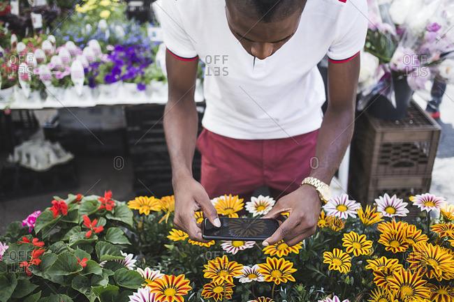 Man taking flower photos in market