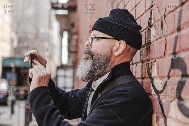 Man taking phone photo in city