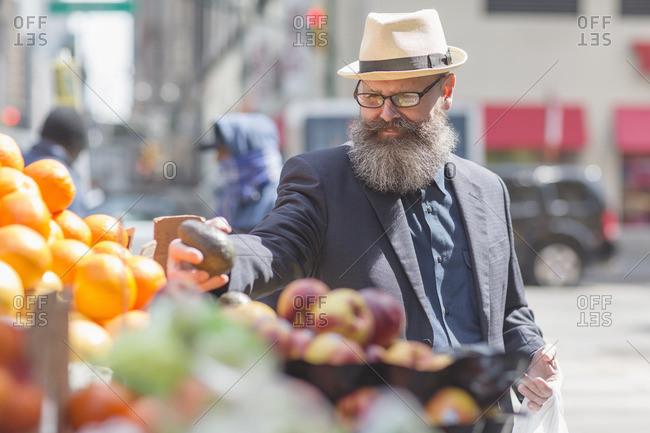 Man with avocado in street market