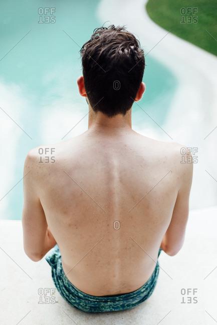 Man sitting alone by pool