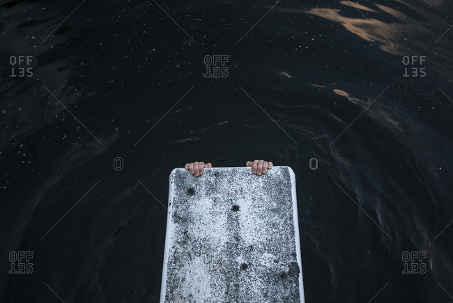 Hands holding diving board