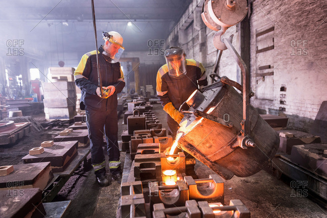 Workers pouring molten metal into molds in foundry