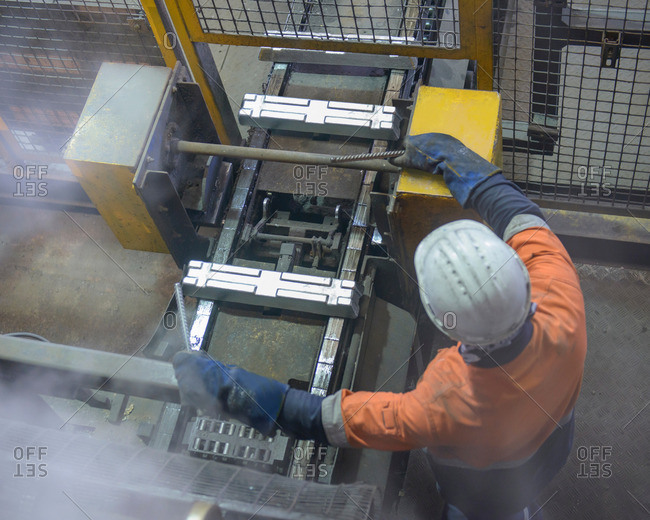 Overhead view of worker with hot ingots in aluminum foundry