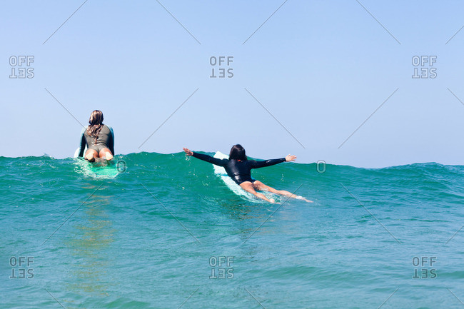 Female friends surfing, Hermosa Beach, California, USA