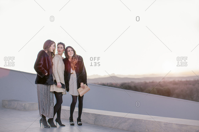 Three female friends standing together at party