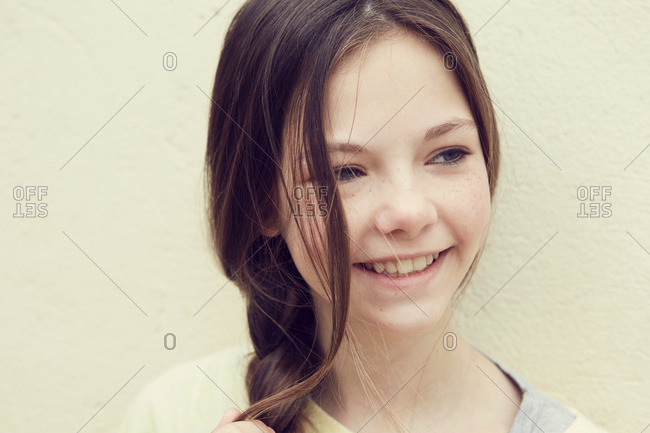 Portrait of smiling girl with plaited hair in front of wall