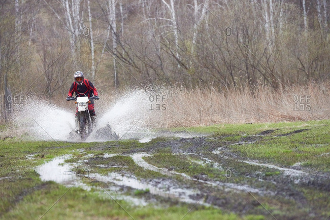 Motocross rider racing on muddy track