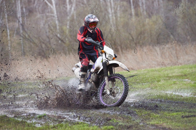 Motocross rider splashing mud on his motorbike