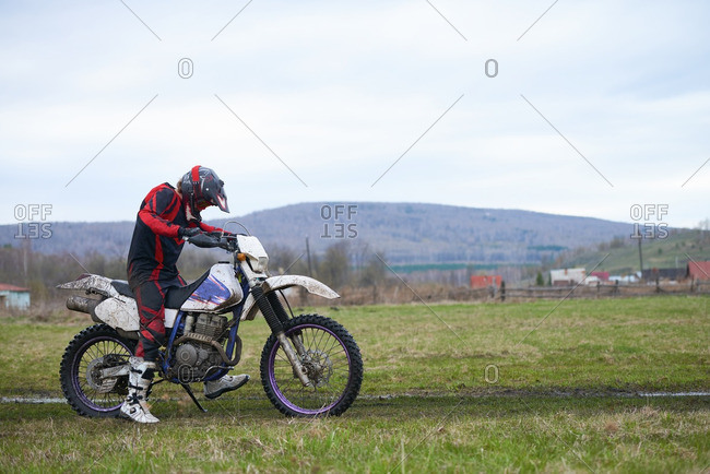 Rider starting his motorcycle in the countryside