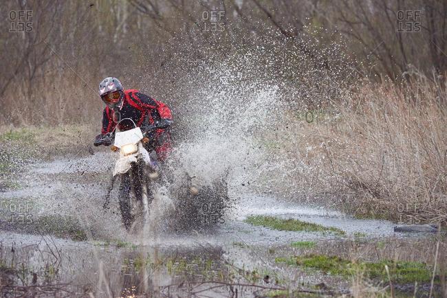 Motocross rider racing in flooded field