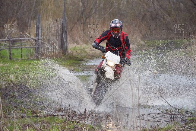 Motocross rider racing in flooded rural area