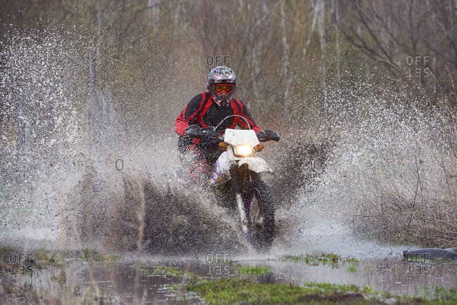 Motocross rider racing in a muddy flooded field