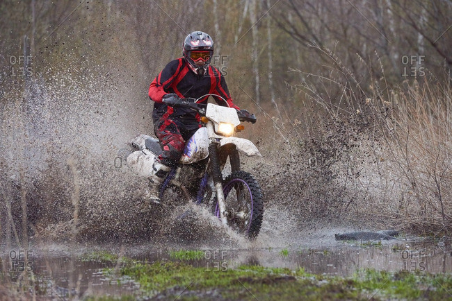 Motocross rider riding in flooded field