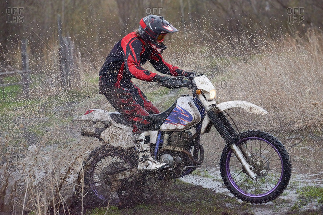 Motocross rider splashing through puddles in the countryside