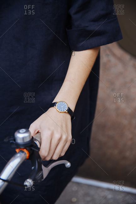 Person wearing a wristwatch holding the handle of a bicycle
