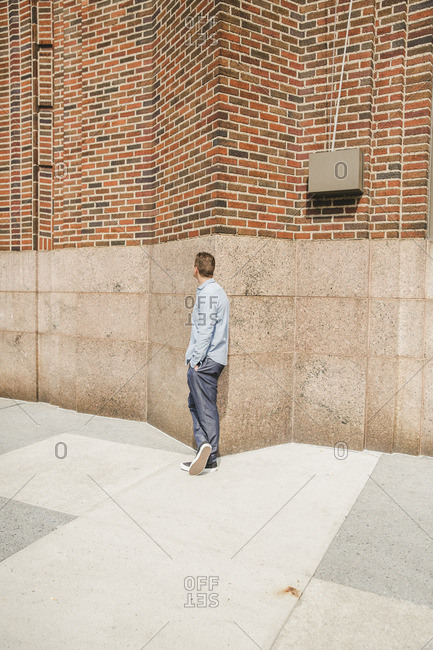 Man leaning against the exterior wall of a building