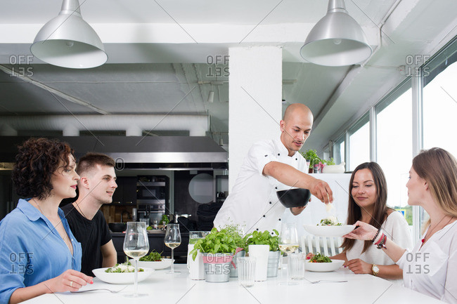 Bald chef serving salad to guests at dinner table