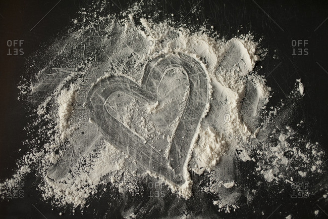 A heart carved from a mound of flour on a table