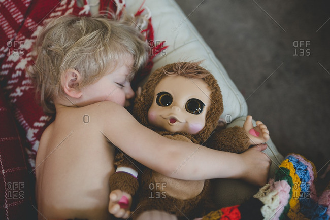 Boy sleeping with a stuffed toy monkey